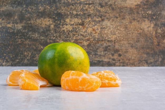 In scheiben geschnittene und ganze frische mandarine.