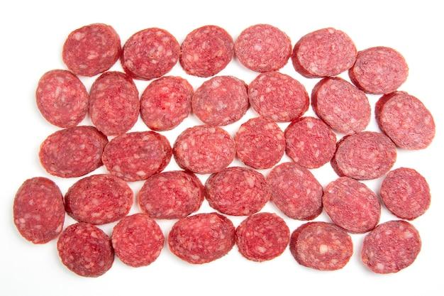 In scheiben geschnittene wurstteile, salami auf weiß.