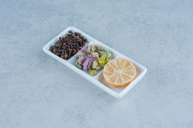 In scheiben geschnittene zitrone, teeblätter und blume in der schüssel auf marmor trocknen.