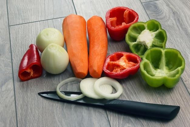 In scheiben geschnittene zwiebeln und pfeffer auf dem küchenbrett und karotten