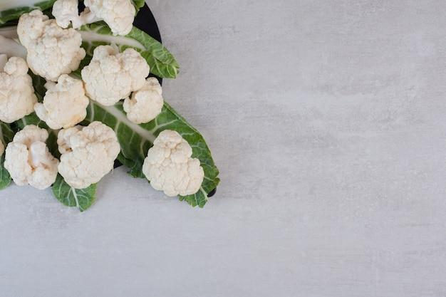 In scheiben geschnittener frischer blumenkohl mit blättern auf schwarzem brett. hochwertiges foto