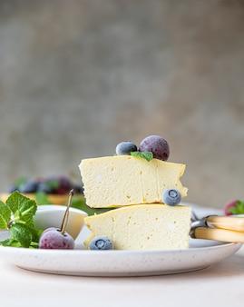 In scheiben geschnittener hüttenkäse-auflauf oder käsekuchen ohne kruste, dekoriert mit beeren und minze