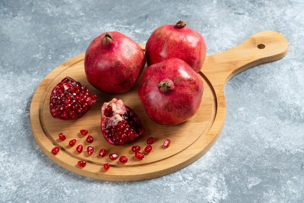 In scheiben geschnittener reifer granatapfel auf einem holzbrett.