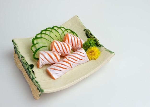 In scheiben geschnittener roher lachssack-sashimi mit gurke auf teller