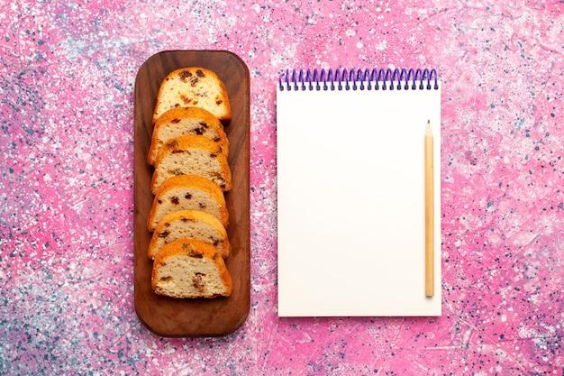 In scheiben geschnittener rosinenkuchen mit notizblock auf rosa oberfläche