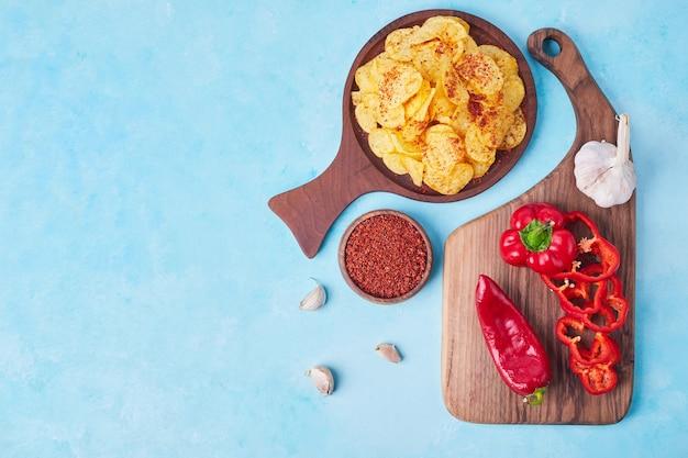 In scheiben geschnittener roter chili und paprika auf einer holzplatte mit gewürzen und crackern beiseite.