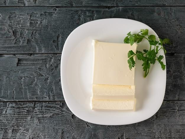 In scheiben geschnittener serbischer käse mit petersilie auf dem dorftisch