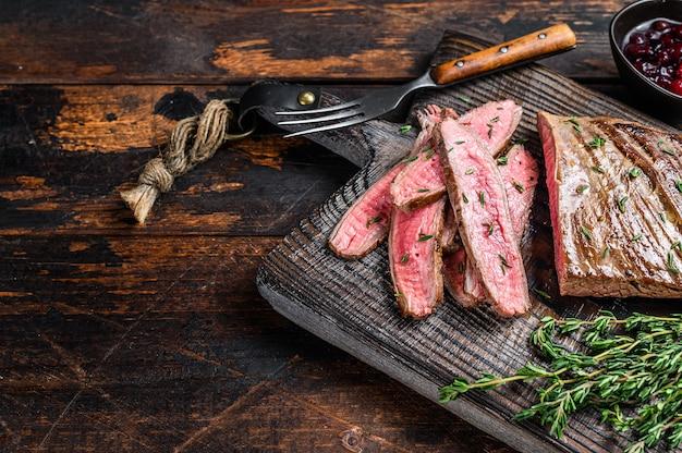 In scheiben geschnittenes flankenrindfleischsteak auf einem hölzernen schneidebrett grillen