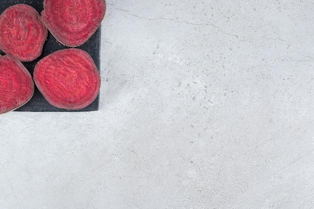 In scheiben geschnittenes frisches rote-bete-gemüse auf einem dunklen brett. foto in hoher qualität