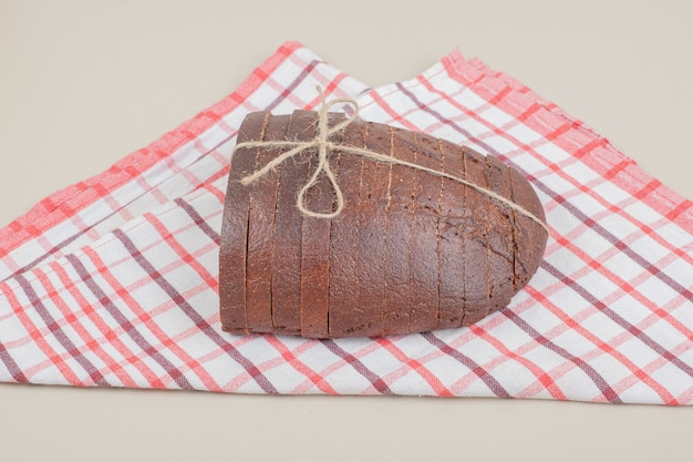 In scheiben geschnittenes frisches schwarzbrot im seil auf tischdecke