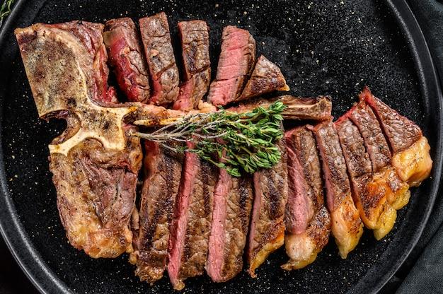 In scheiben geschnittenes gegrilltes florentiner steak. t knochenfleisch rindfleisch. schwarzer raum. draufsicht