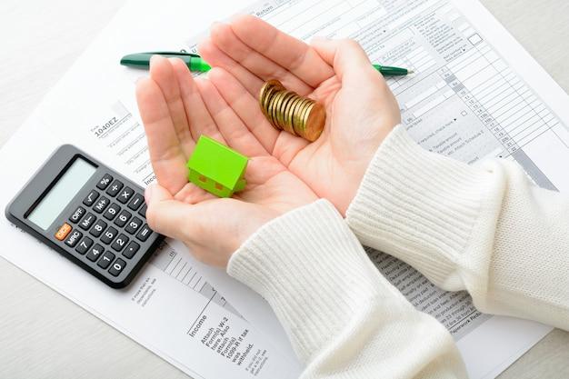 In seinen händen ein stapel münzen und papier über dem haus über steuererklärungsrechner