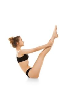 In sich selbst verliebt. schöner weiblicher körper lokalisiert auf weißer wand. sportlicher, sinnlicher body mit gepflegter haut in unterwäsche.