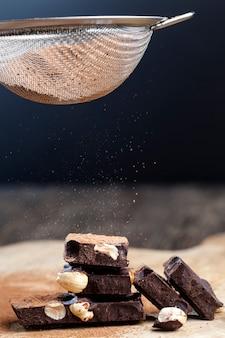 In teile geteilte tafelschokolade mit ganzen nüssen, süße schokolade mit in stücke gebrochenen nüssen, schokoladenstücke mit haselnüssen mit kakao und zucker