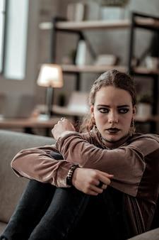 In tränen ausbrechen. stilvoller dunkelhaariger teenager, der sich einsam und isoliert fühlt und in tränen ausbricht
