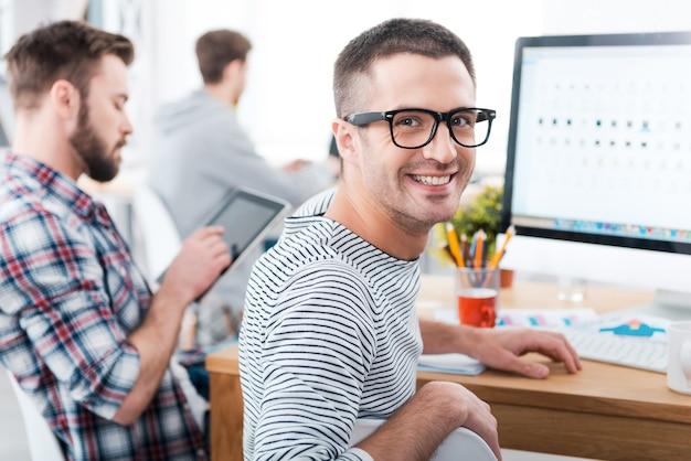 In unserem büro halten wir es locker. glücklicher junger mann, der über die schulter schaut und lächelt, während er mit seinen kollegen am schreibtisch sitzt, die im hintergrund arbeiten