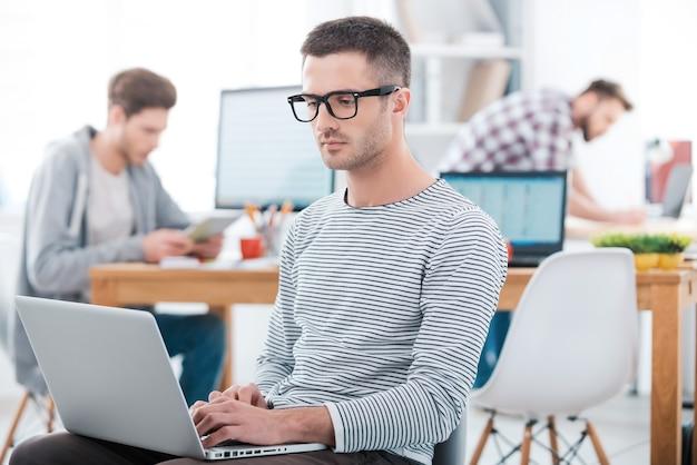 In unserem büro können wir nach belieben arbeiten. ernster junger mann, der am laptop arbeitet, während zwei leute im hintergrund arbeiten