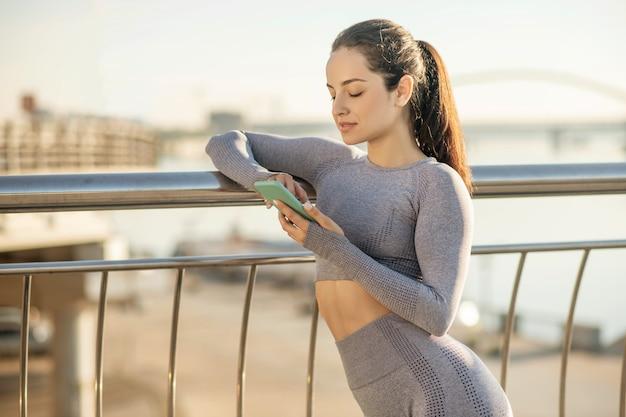 In verbindung gebracht. ein süßes mädchen in grauer sportkleidung mit einem smartphone in der hand