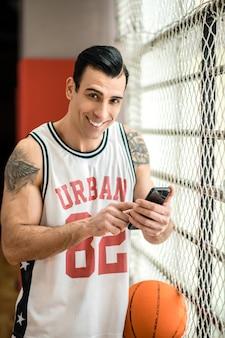 In verbindung gebracht. junger sportler mit tätowierung, die ein smartphone in seinen händen hält
