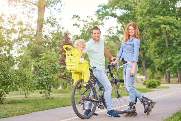In voller länge aufnahme einer glücklichen jungen familie, die zusammen radfahren und inlineskaten im örtlichen park genießt.