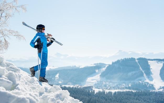 In voller länge aufnahme einer skifahrerin, die mit ihren skiern auf der schulter den hang hinuntergeht. winterskigebiet und berge