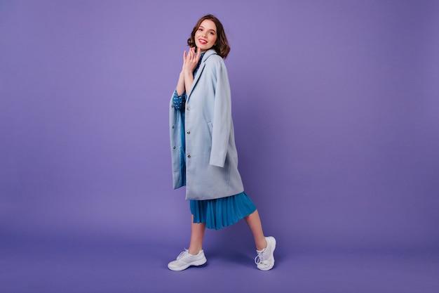 In voller länge aufnahme eines fröhlichen mädchens in weißen turnschuhen und midikleid. dame mit gewelltem haar, das im stilvollen blauen mantel aufwirft.
