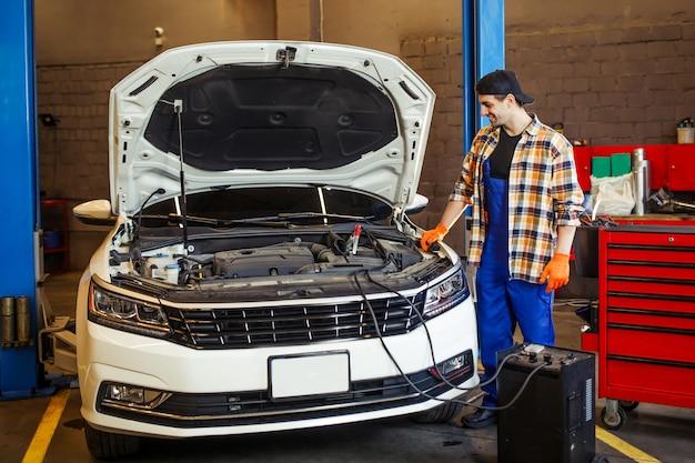 In voller länge aufnahme eines gutaussehenden automechanikers, der die batterie mit drahtkabeln in einer modernen tankstelle auflädt