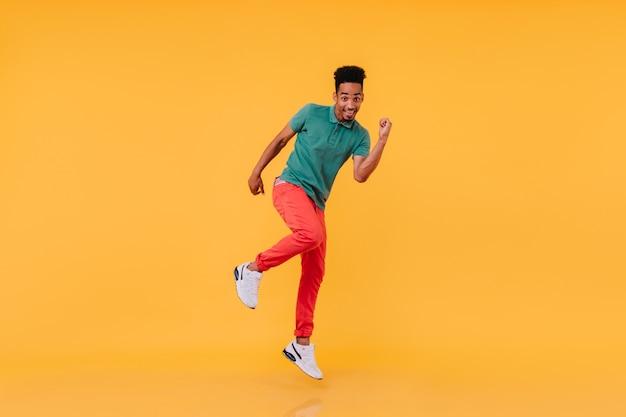 In voller länge aufnahme eines inspirierten schwarzen mannes, der in roten hosen tanzt. innenfoto des sorglosen afrikanischen mannes, der genießt.