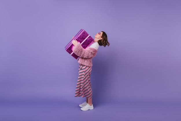 In voller länge aufnahme von erstaunlichen geburtstagskind in weißen turnschuhen, die ihr geschenk halten. lockiges weibliches modell in der rosa jacke, die mit geschenk aufwirft.