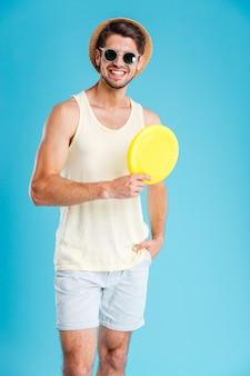 In voller länge des fröhlichen jungen mannes, der frisbee-scheibe über blauer wand hält?
