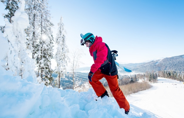 In voller länge ein freerider-snowboarder, der sein snowboard trägt und auf den berg klettert