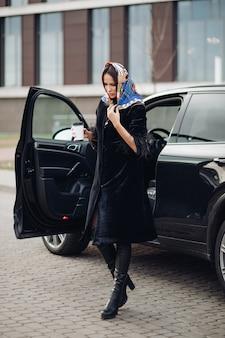 In voller länge einer modischen dame in schwarzem mantel und lederstiefeln, die ein buntes taschentuch um den hals trägt. sie trägt eine tasse kaffee zum mitnehmen gegen offenes auto auf der straße.