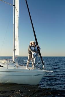 In voller länge eines glücklichen seniorenpaares, das sich umarmt und den horizont betrachtet, während es eine atemberaubende aussicht genießt