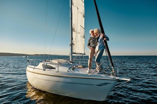 In voller länge eines glücklichen seniorenpaares in liebesmann und -frau, die auf der seite des yachtdecks stehen