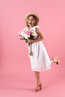 In voller länge eines schönen fröhlichen jungen blonden mädchens, das ein sommerkleid trägt, das isoliert über einer rosa wand steht und einen strauß pfingstrosen hält, posiert