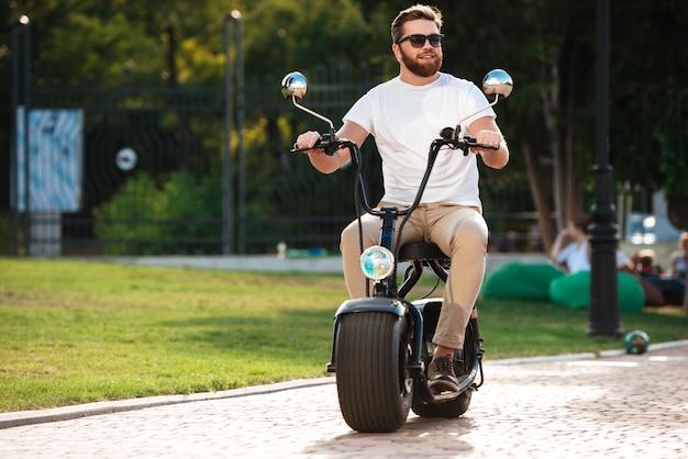 In voller länge fährt ein glücklicher bärtiger mann mit sonnenbrille auf einem modernen motorrad im freien und schaut weg