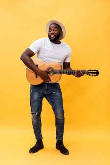 In voller länge foto des aufgeregten künstlerischen mannes, der seine gitarre in der zufälligen reihe spielt. auf gelbem hintergrund isoliert.