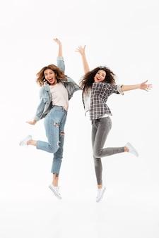 In voller länge freuen sich zwei frohe mädchen und springen über weiße wand