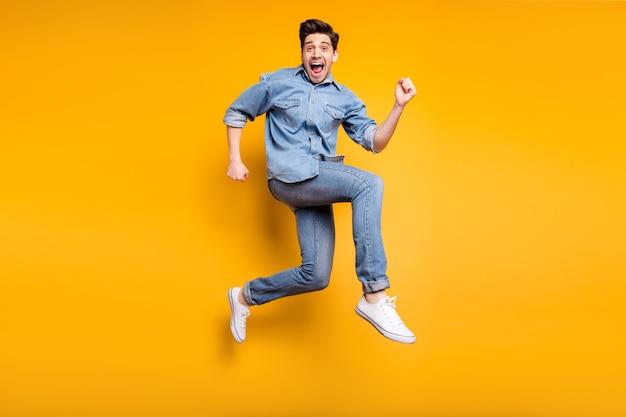 In voller länge gedreht körpergröße foto von fröhlichen positiven verrückten mann dringend für verkauf und rabatt in weißen turnschuhen denim isoliert lebendige farbe wand
