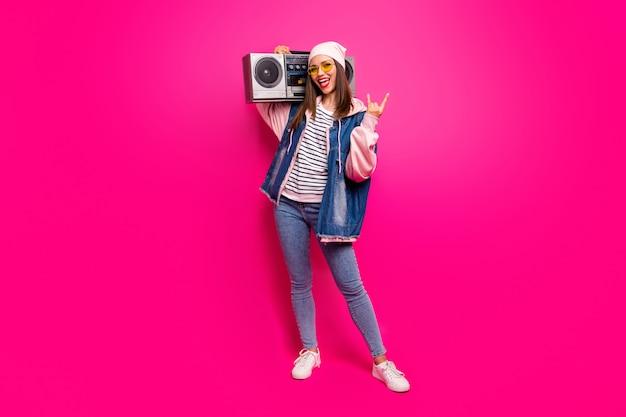 In voller länge körpergröße ansicht von ihr sie schöne attraktive funky coole fröhliche fröhliche mädchen tragen boombox zeigt horn zeichen mit spaß isoliert auf hellen lebendigen glanz lebendige rosa fuchsia farbe