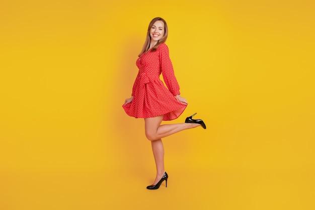 In voller länge körpergröße des fröhlichen lustigen mädchentanzes halten roten minirock viel spaß an der gelben wand