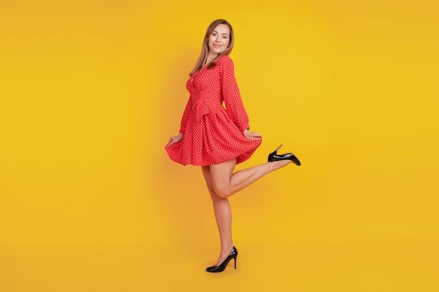 In voller länge körpergröße des sorglosen funky mädchentanzes halten roten minirock viel spaß an der gelben wand