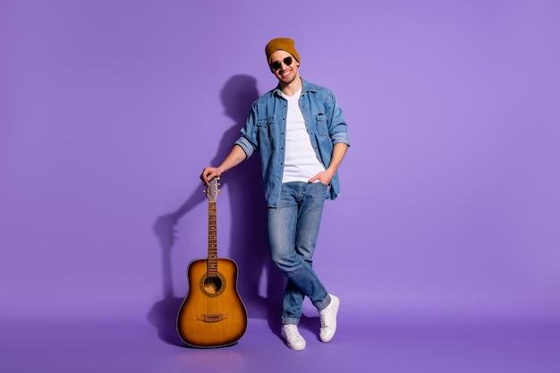 In voller länge körpergröße foto des fröhlichen positiven niedlichen attraktiven attraktiven musikmachers, der sich auf seine gitarre stützt, die mütze turnschuhe schuhe isoliert lila hellen farbe hintergrund trägt