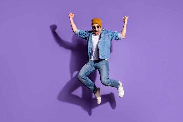 In voller länge körpergröße foto des fröhlichen verrückten positiven positiven starken schreienden schreienden mannes mit ekstatischem gesichtsausdruck lokalisiert über lila lebendigem farbhintergrund