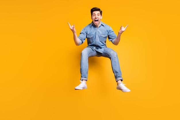 In voller länge körpergröße foto von fröhlich schreienden verrückten überglücklichen mann gefühl eindruck nach dem besuch konzert seiner lieblings-rock-band zeigt gehörnten finger isoliert lebendige farbe wand