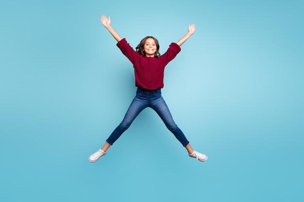 In voller länge körpergröße foto von fröhlichen lockigen positiven preteen shaping star mit ihren beinen arme springen frei isoliert lebendige blaue farbe hintergrund