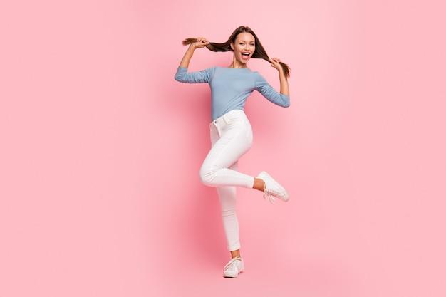 In voller länge körpergröße foto von fröhlichen positiven niedlichen hübschen mädchen zeigt ihr gesundes haar springen tanzen isoliert pastellfarbe hintergrund