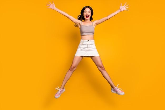 In voller länge körpergröße foto von fröhlichen positiven niedlichen hübschen netten freundin springenden formstern mit beinen arme isoliert lebendigen farbhintergrund