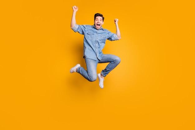In voller länge körpergröße foto von fröhlichen positiven verrückten mann springen schreiend zu jedem tragen weiße turnschuhe isoliert lebendige farbwand