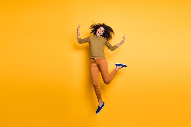 In voller länge körpergröße foto von lockigen gewellten hübschen süßen aufgeregten verrückten girlfried tragen orange hose hosen schuhe grünen speater isoliert über gelb lebendigen farbhintergrund
